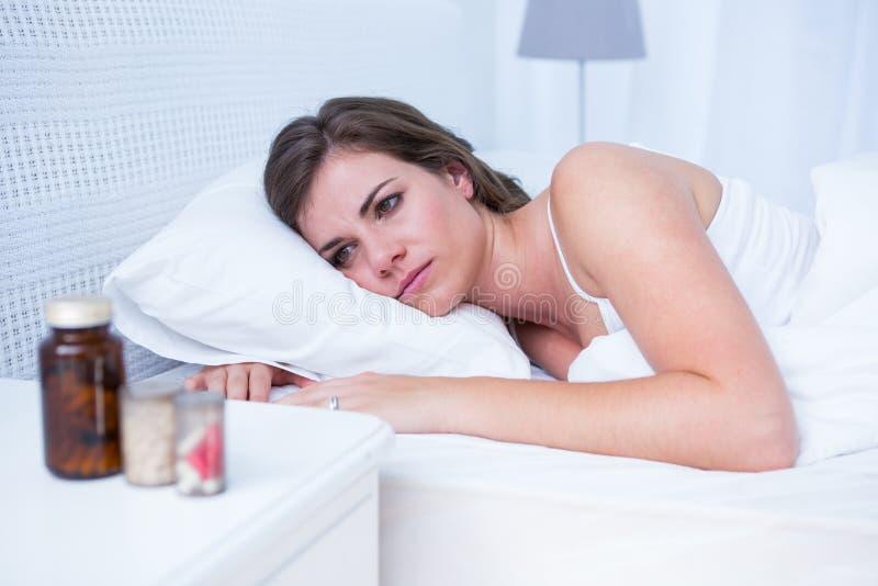 哀伤的妇女在床上的看药片 库存图片