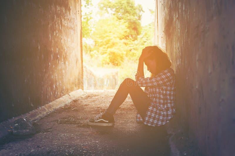 哀伤的妇女拥抱她的膝盖并且哭泣感到很坏,寂寞,悲伤