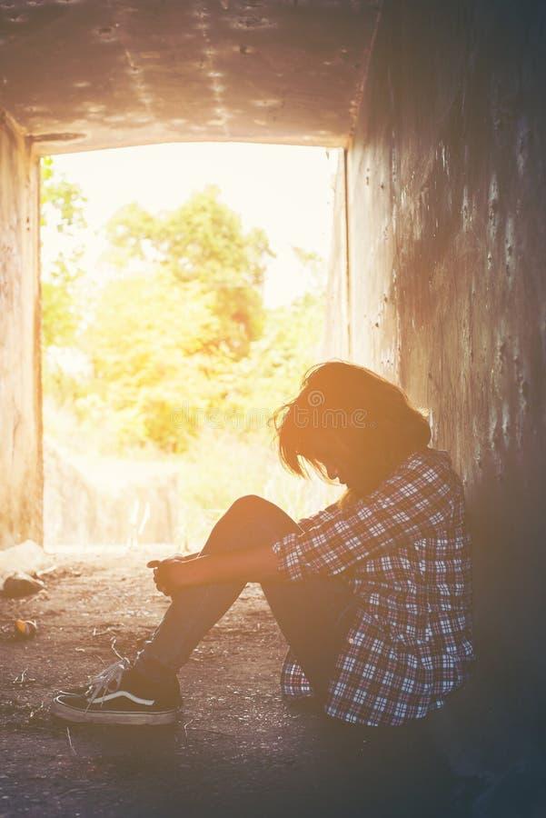 哀伤的妇女拥抱她的膝盖并且哭泣感到很坏,寂寞,悲伤 免版税库存图片