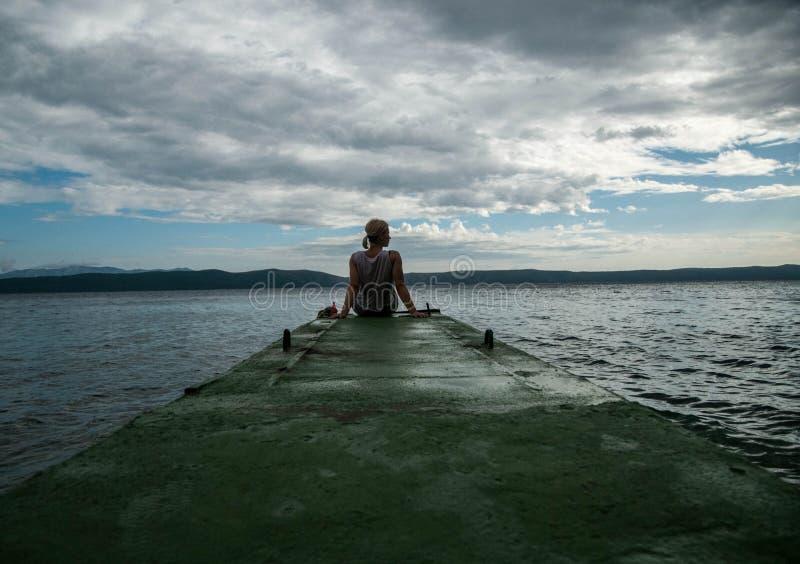 哀伤的妇女 女孩消沉、重音和问题,痛苦,女性沮丧 少妇坐看在天际的码头 免版税库存图片