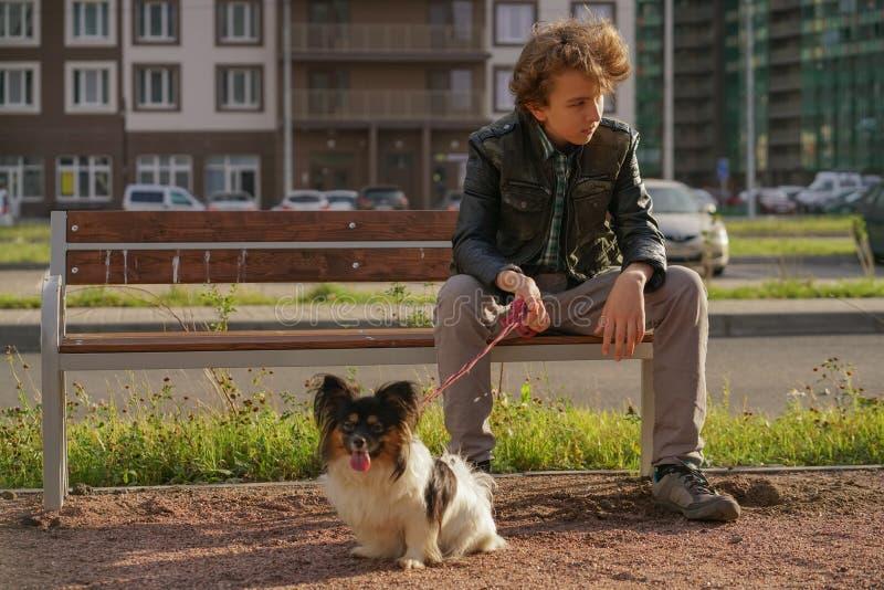 哀伤的孤独的人坐与他的狗的一条长凳 青春期困难在通信概念的 库存图片
