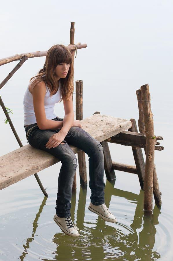 哀伤的孤独的十几岁的女孩坐小的木码头 库存照片