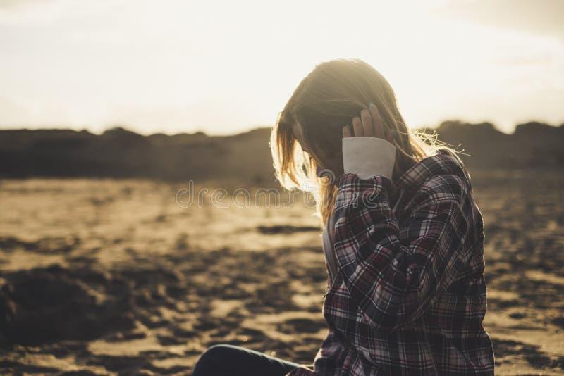哀伤的孤独的女孩坐下在海滩在日落的黄昏期间-金黄颜色和沙子在背景中人的爱是 免版税库存图片