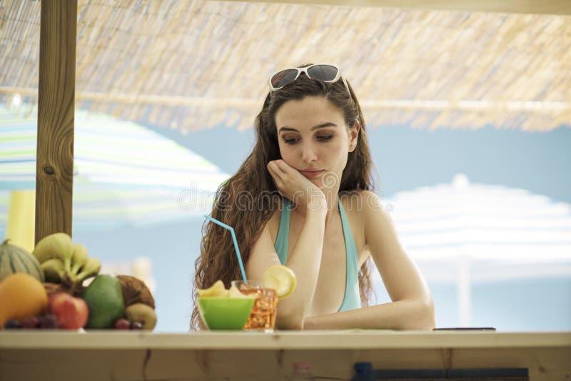 哀伤的孤独的妇女喝一杯在海滩 免版税图库摄影