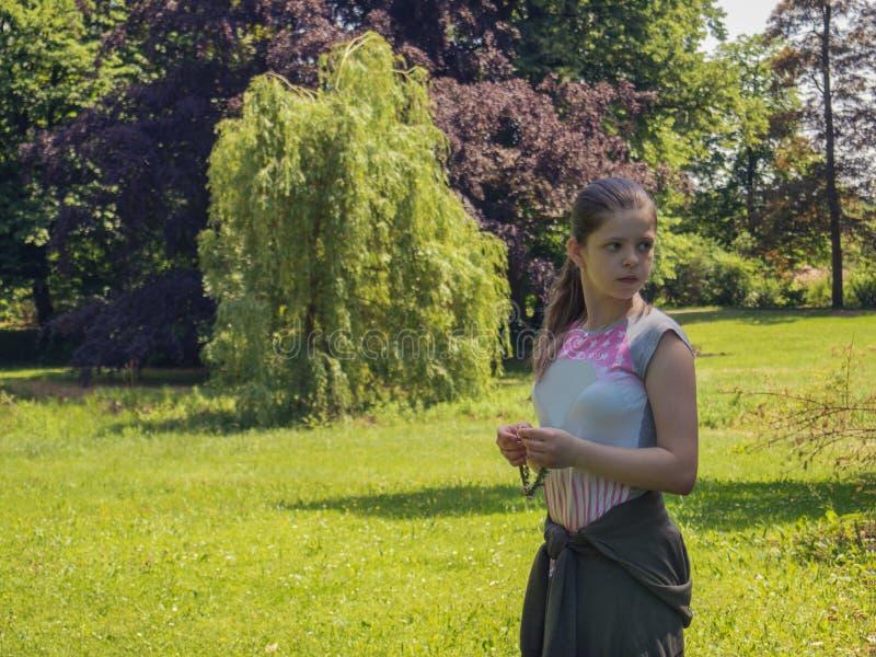 哀伤的孤独的白种人十几岁的女孩在背景的树包围的公园 免版税库存照片