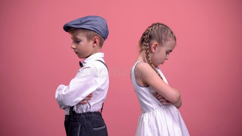 哀伤的孩子在沈默结合站立在争吵,被隔绝的桃红色背景以后 免版税库存图片