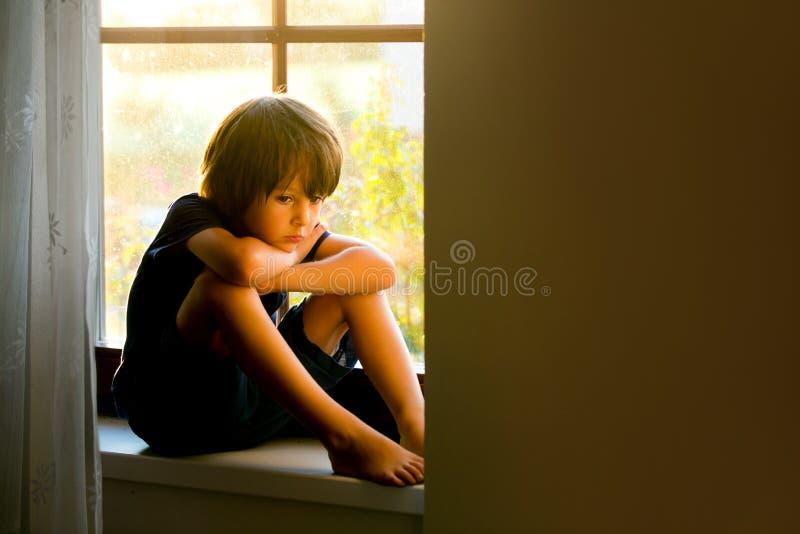 哀伤的孩子,男孩,坐窗口盾 免版税库存图片