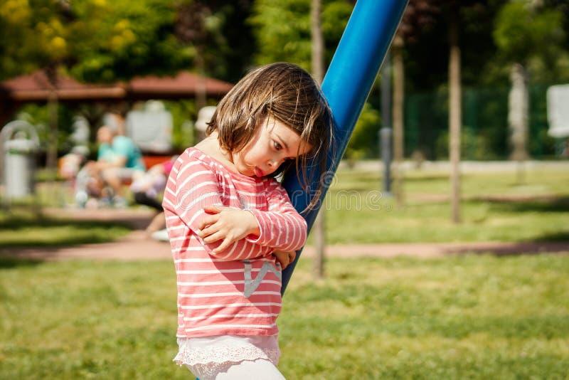 哀伤的小女孩在摇摆旁边站立在操场 免版税库存照片