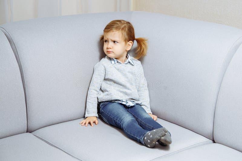 哀伤的小女孩坐长沙发在房子的客厅 库存图片
