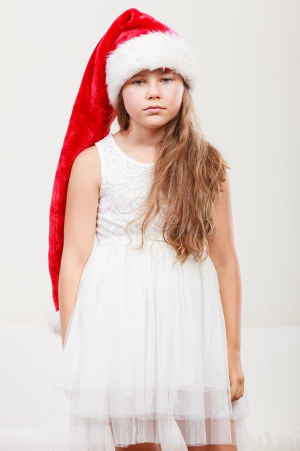 哀伤的小女孩孩子在圣诞老人帽子 圣诞节 库存图片