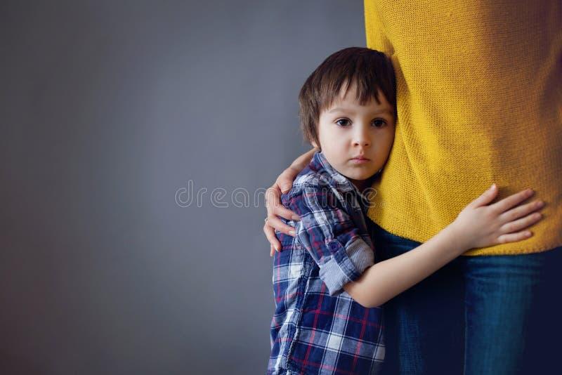 哀伤的小孩,男孩,在家拥抱他的母亲 免版税库存图片