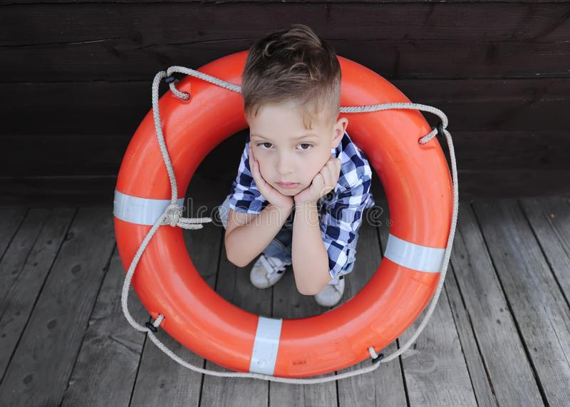 哀伤的小男孩坐与lifebuoy的木地板 免版税库存照片