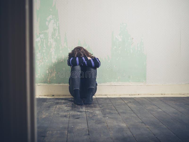 哀伤的少妇坐地板在空的屋子里 免版税图库摄影
