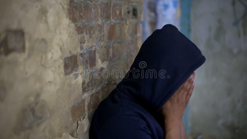 哀伤的少年哭泣在被放弃的房子里的,生活毁坏被战争,哀痛和哀情 图库摄影