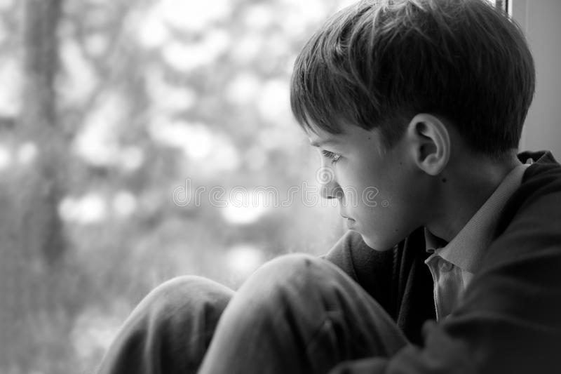 哀伤的少年坐窗口 免版税库存照片