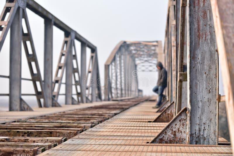 哀伤的少年画象消沉的坐桥梁在 免版税库存照片