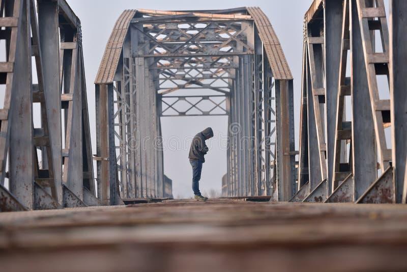 哀伤的少年画象消沉的坐桥梁在 库存图片