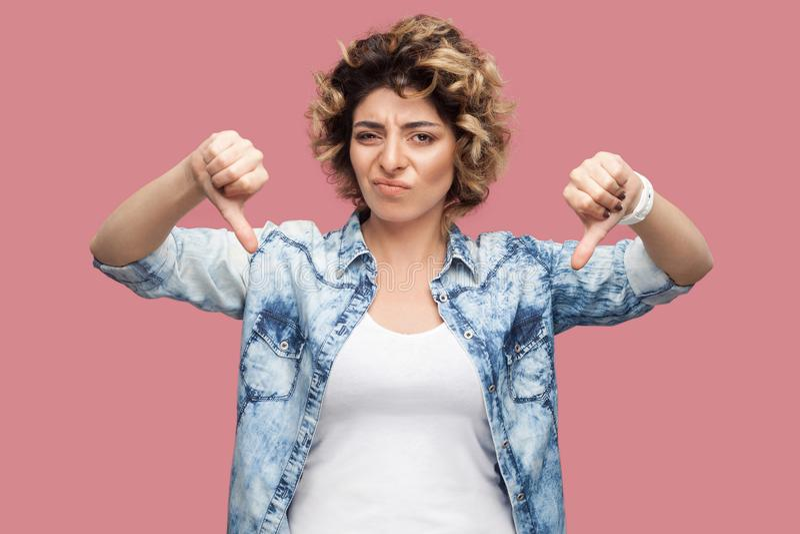 ?? 哀伤的年轻女人画象有下来卷曲发型的在偶然蓝色衬衣身分,拇指和看照相机与 免版税库存照片