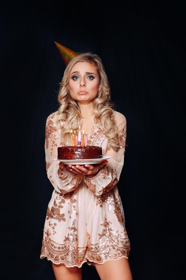 哀伤的年轻美丽的白肤金发的妇女藏品生日蛋糕的画象与蜡烛的 库存图片