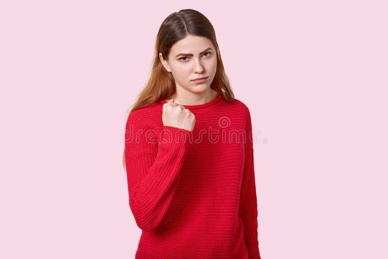 哀伤的恼怒的年轻欧洲妇女照片有平直的黑发的,显示拳头在照相机,穿戴在红色套头衫,摆在玫瑰色 免版税图库摄影