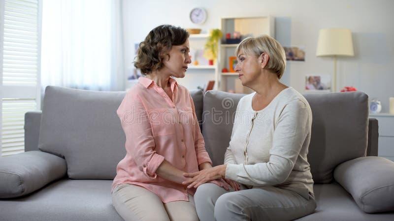 哀伤的成熟握手和看彼此,支持的妇女和女儿 库存照片