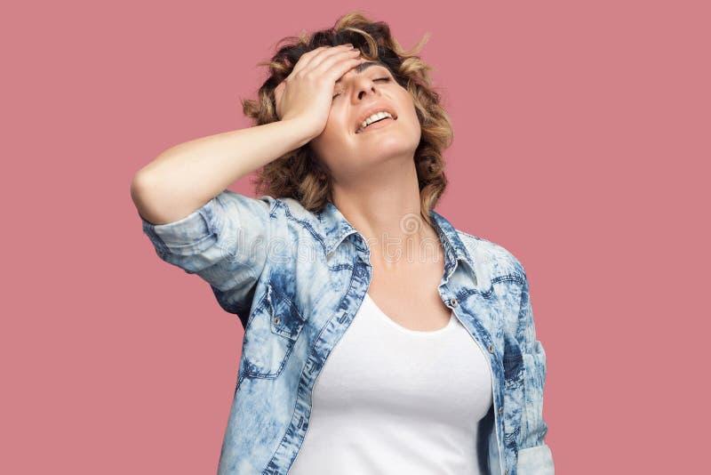 哀伤的担心的年轻女人画象有卷曲发型的在偶然蓝色衬衣身分,握在前额的手和哀伤,因为 免版税库存照片