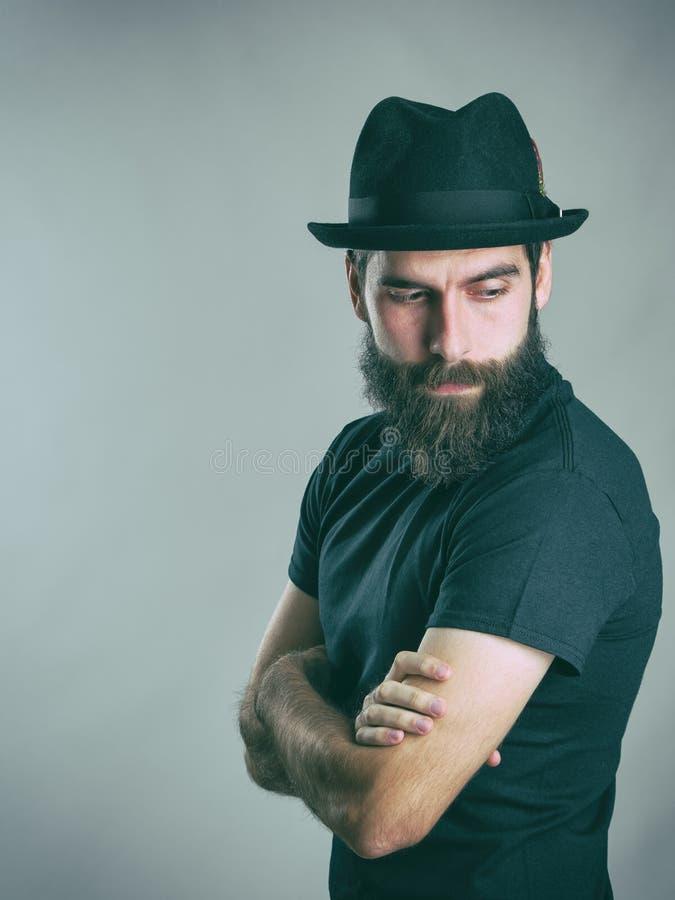 哀伤的有胡子的时髦的回顾在肩膀的人佩带的帽子侧视图  图库摄影