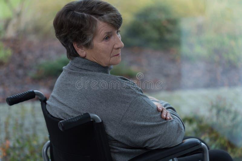 哀伤的残疾资深妇女 免版税库存照片