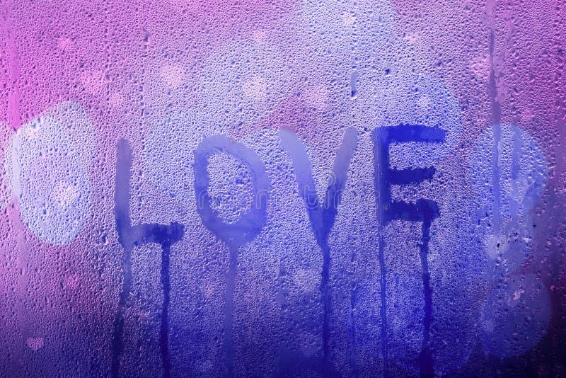 哀伤的爱词手写在湿窗口 库存照片