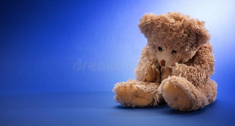 哀伤的玩具熊,拿着他的头,坐在蓝色空的室背景中,拷贝空间 库存图片