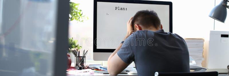 哀伤的生气男性工作者拿着他的解决业务问题的头 免版税库存照片