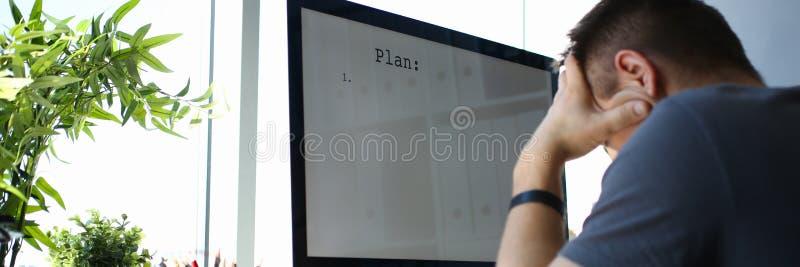 哀伤的生气男性工作者拿着他的解决业务问题的头 免版税库存图片