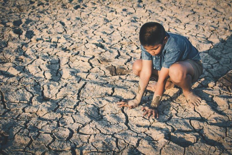 哀伤的男孩坐破裂的干燥地面 库存图片