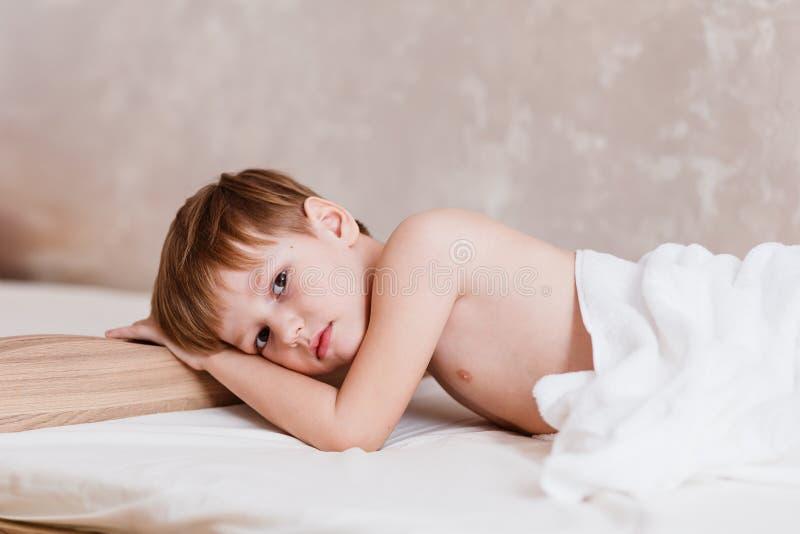哀伤的男孩说谎在床上的六岁 库存照片