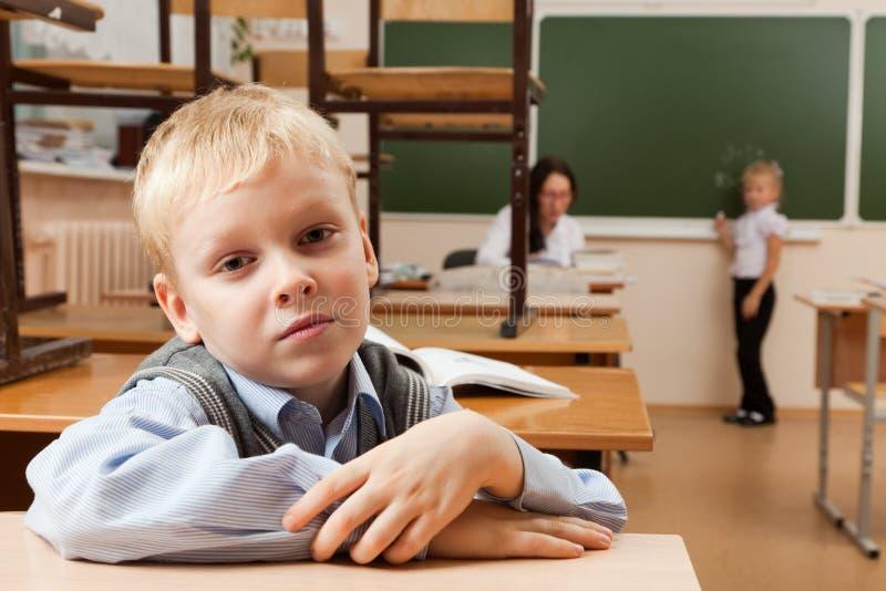 哀伤的男小学生在教室 免版税库存图片