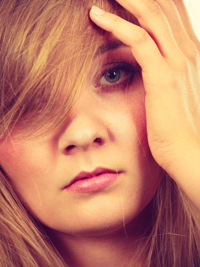 哀伤的白肤金发的妇女用在面孔的手 库存图片