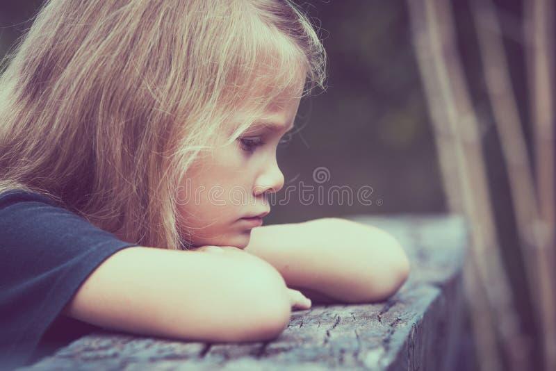 哀伤的白肤金发的小女孩画象坐桥梁 库存照片