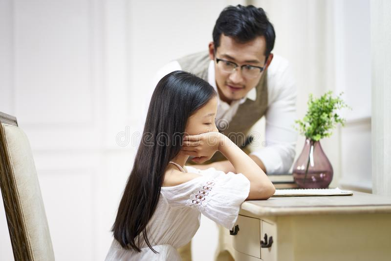 哀伤的矮小的亚裔女孩从父亲得到舒适 库存照片