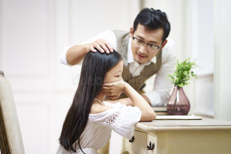 哀伤的矮小的亚裔女孩从父亲得到舒适 库存图片