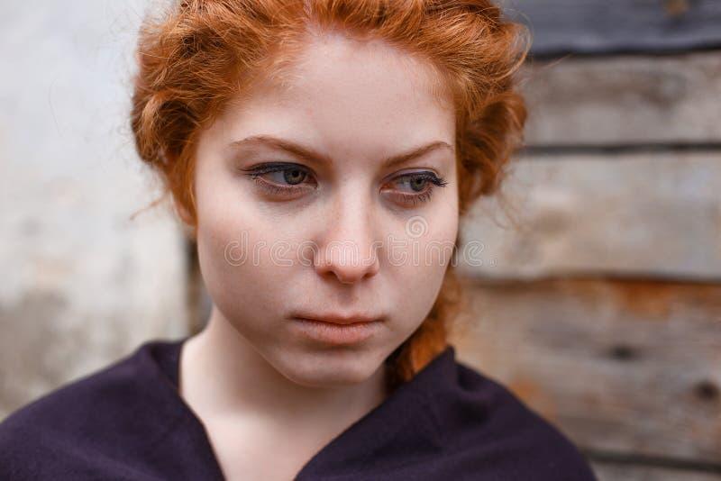 哀伤的红发女孩、悲伤和忧郁的画象在她的眼睛 免版税库存照片