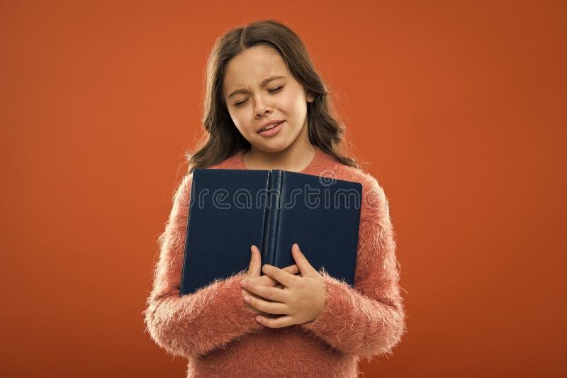哀伤的结束的故事 女孩举行书读了在橙色背景的故事 孩子享用看书 书店概念 免版税库存图片