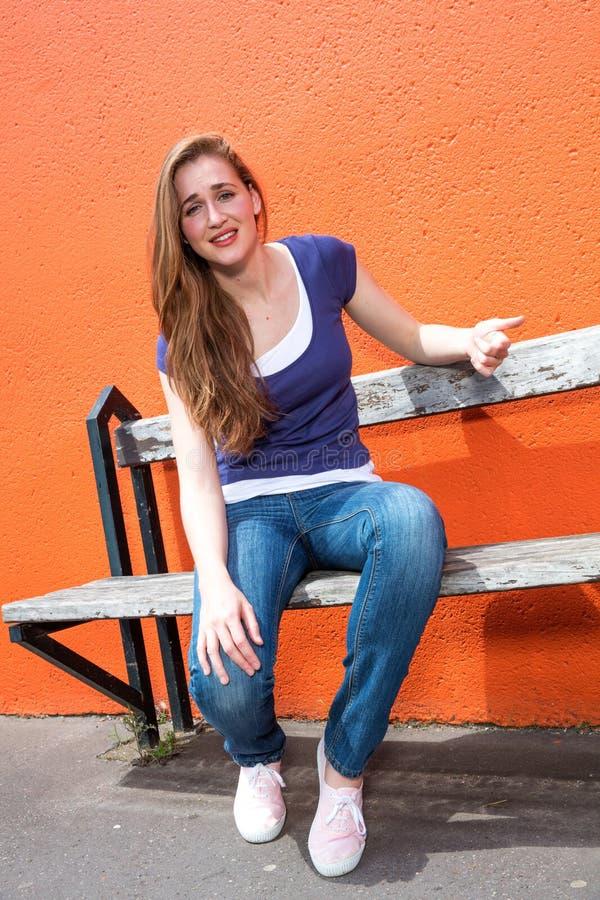 哀伤的美丽的女孩坐长凳,抱怨,表示失望 免版税库存图片
