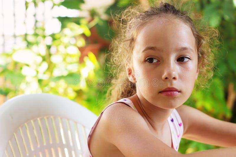 哀伤的美丽的小女孩看与严肃的面孔在su 免版税库存图片