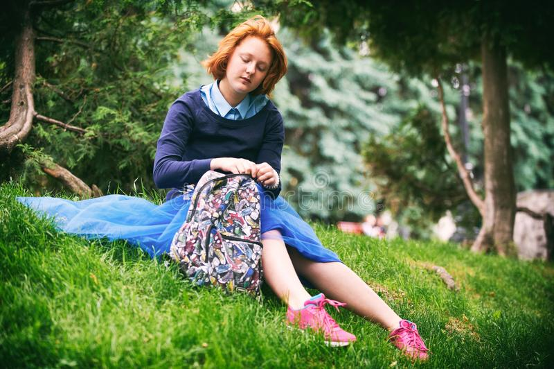 哀伤的美丽的少妇坐草 免版税库存照片