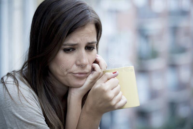 年轻哀伤的美丽的看起来妇女遭受的消沉担心和浪费在家庭阳台 免版税库存照片