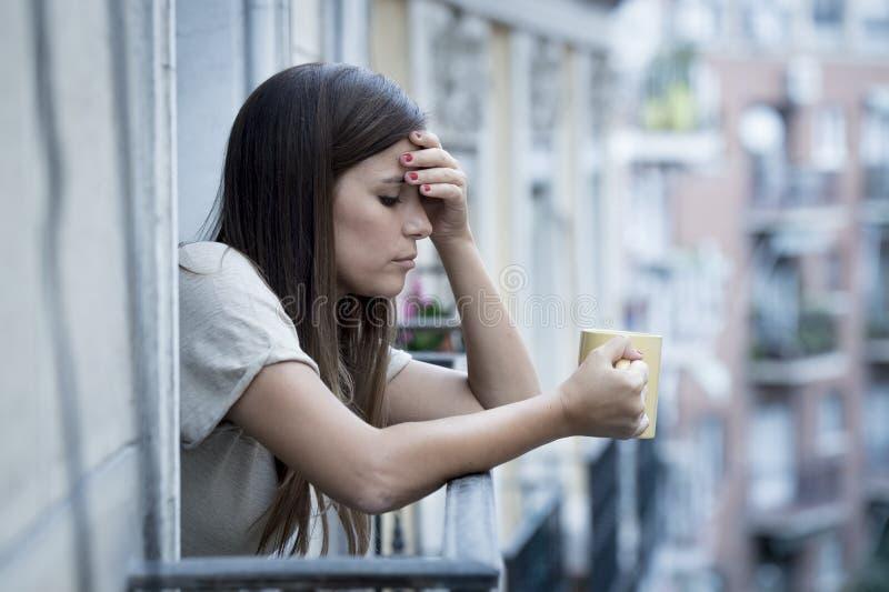 年轻哀伤的美丽的看起来妇女遭受的消沉担心和浪费在家庭阳台 库存图片