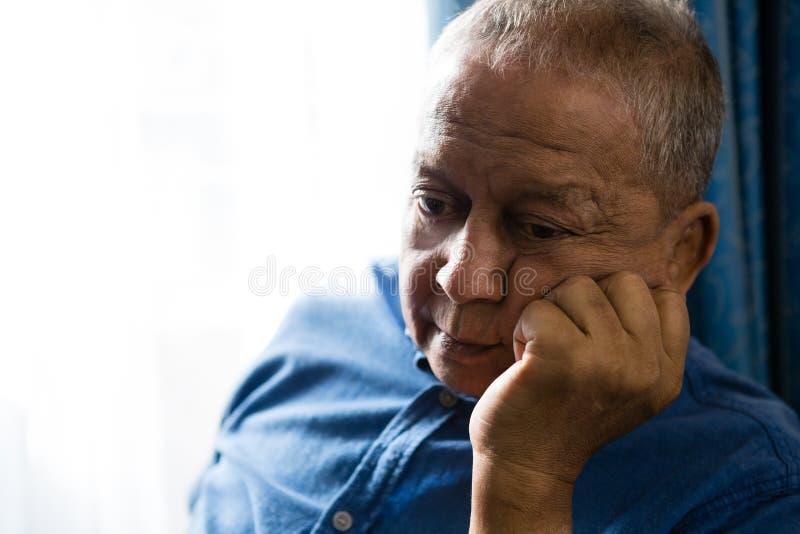 哀伤的老人用在坐由窗口的下巴的手 免版税库存图片