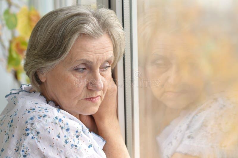 哀伤的老妇人在家 免版税库存照片
