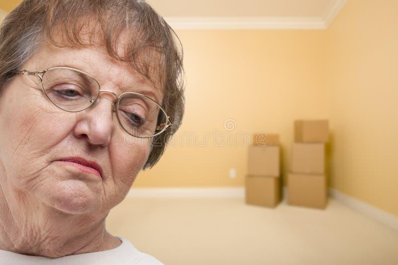 哀伤的老妇人在有配件箱的空的屋子里 免版税图库摄影