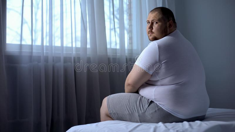 哀伤的肥胖人在家坐床,看照相机,消沉,不可靠 库存图片